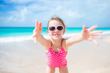 Happy little girl taking selfie at tropical beach on exotic island