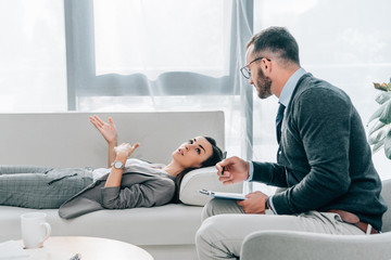 side view of patient lying on sofa and talking with psychologist in office