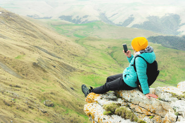 Rear view of a woman sitting on a rock in winter clothes and wearing a hat on a smartphone. Caucasus Mountains