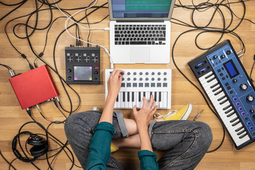 Woman making electronic music on laptop computer and digital instruments. Top view of young female producing modern indie music on synthesizer and digital controllers