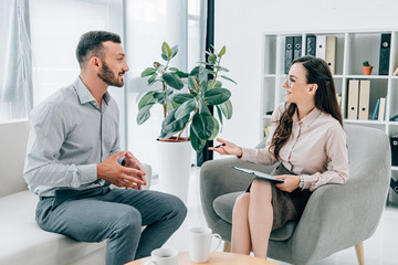 smiling psychiatrist with clipboard talking with happy patient in office