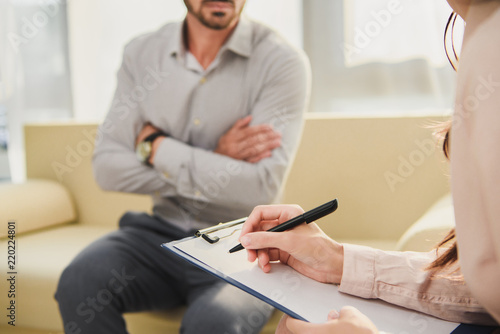 Cropped View Of Patient And Psychologist Writing Diagnosis In