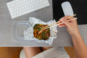 Young woman eating warm salad ordered in food delivery company. Chinese cuisine at the working desk