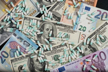 A bunch of pills and tablets on euro and dollar banknotes