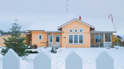 Beautiful Winter View of the Idyllic House with Gorgeous Backyard and a Fence. Soft Snow Falls on a Winter Day.