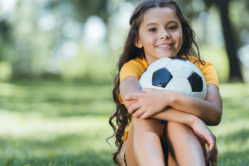 adorable happy child holding soccer ball and smiling at camera in park