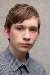 Portrait of the young Russian man at a brick wall