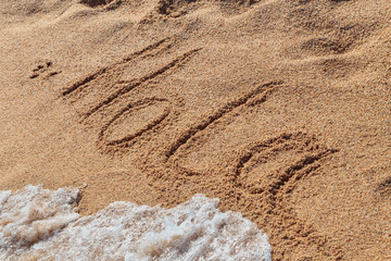 inscription HOLA on the beach sand