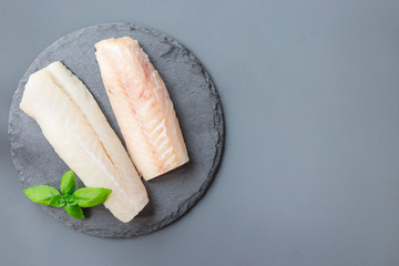 Fresh raw cod fillet with basil on stone plate, horizontal, copy space, top view