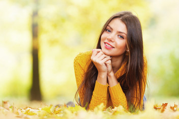 Cute woman laying in autumn park