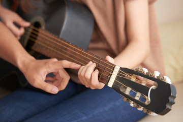 Cropped image of young woman attending acoustic guitar class