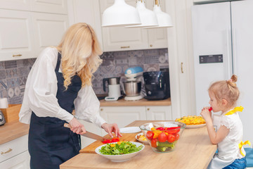 Mother and daughter with a knife cuts red pepper at the kitchen table, cooking concept.