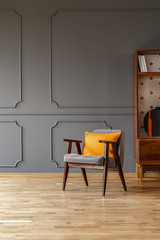 Orange pillow on grey armchair in vintage flat interior with wooden floor and cabinet. Real photo