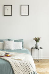 Pale sage and white linen, pillows and a blanket on a bed standing against white wall with two pictures in a bedroom interior. Black metal side table by the bed. Real photo