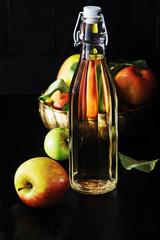 Apple cider vinegar and  apples on black wooden background.