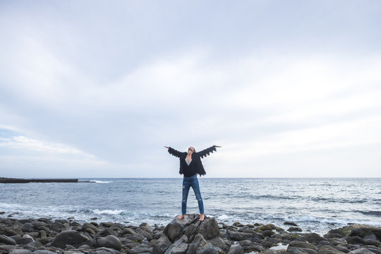Indie young caucasian woman standing with open arms and enjoy the nature and the freedom alone on the rocks at the beach. ocean in background. casual clothes and wanderlust concept