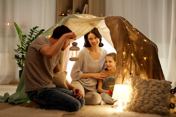 family, hygge and people concept - happy mother, father with lantern and little daughter playing in kids tent at night at home