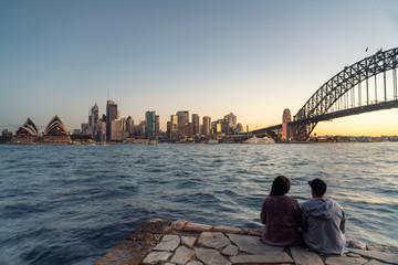 Romantic couple looks at Sydney skyline at dusk in Sydney New South Wales, Australia.