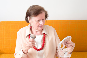 Seniorin schminkt sich