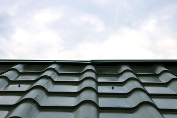 New green roof of house made of iron shingles against blue sky background closeup