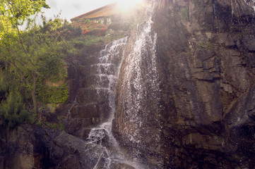 waterfall in sun rays view from below