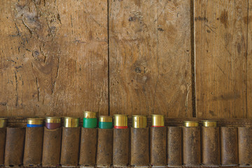 Vintage leaither belt with cartridges on old wooden background with copy space