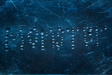 the word monster is written in English with drops of water on a dark blue background with scratches