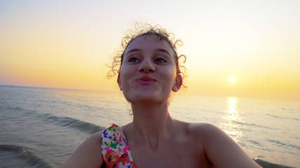 Selfie of young teen holding camera and turning on beach at sunset