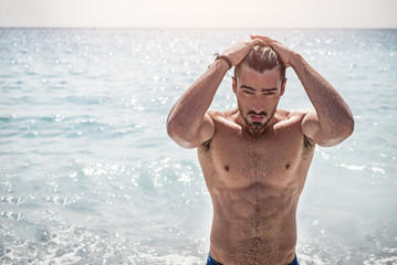 Handsome muscular young man standing on a beach, relaxed, taking a bath, wearing bathing suit Wall mural