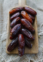 Fresh dates on a wooden old tray lying on the table.