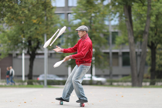 A man in a cap juggles with clubs, standing on small wheels on the street of a European city