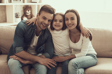Portrait of Young Happy Family Sitting on Sofa