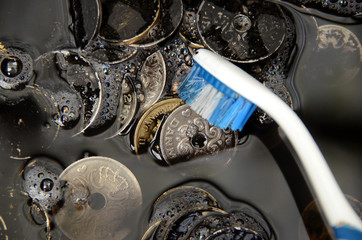 "Black Danisk Krone coins being washed, suggesting the term ""whitewash of black money"""
