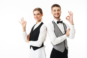 Young smiling waiter and waitress in white shirts and vests sstanding back to back happily looking in camera while showing ok gestures over white background