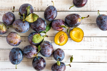 Plums on a white rustic wooden background. Juicy fresh blue plums close-up. Flat lay, top view, copy space