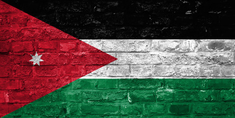 Flag of Jordan over an old brick wall background, surface