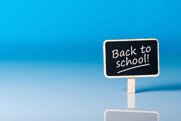 Back to school - Message at little plate at blue background. Education concept, 1 september time