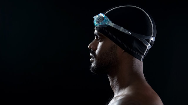 Determined male swimmer prepared for relay, looking at pool, close up of face