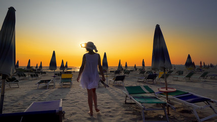 Sexy woman having fun walking, jumping, turning on empty beautiful beach with straw umbrellas and beds against sunset, cinematic shot