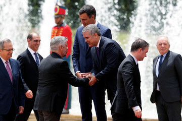 Colombian President Ivan Duque shakes hands with a member of the Spanish delegation who is joining Spanish Prime Minister Pedro Sanchez in an official ceremony at the presidential palace in Bogota