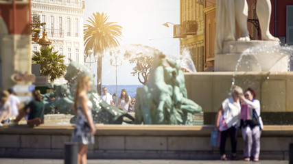 People walking by and taking pictures near Sun Fountain in Nice, city life