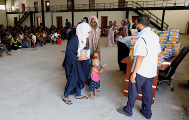 Migrants are seen in a shelter after they were relocated from government-run detention centers, after getting trapped by clashes between rival groups in Tripoli