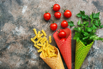Pasta,tomatoes and parsley in a waffle cone from the ice cream. The concept of food. The view from the top,flat lay.