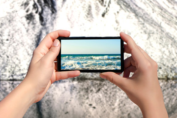 Woman's hands taking picture on mobile phone of summer beach on snowy mountains background. Concept of changing of the seasons
