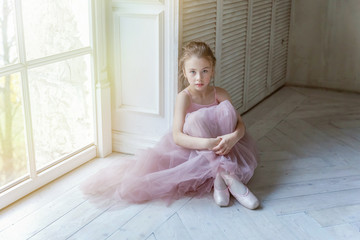 Young classical ballet dancer girl in dance class. Beautiful graceful ballerine in pink tutu skirt puts on pointe shoes near large window in white light hall