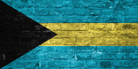 Flag of Bahamas over an old brick wall background, surface