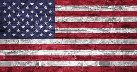 Flag of United States of America over an old brick wall background, surface. USA flag