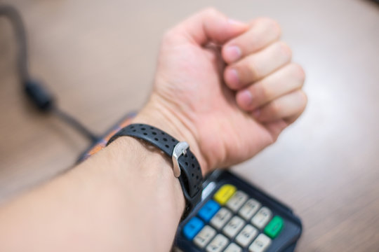 Contact less payment. Paying with smart bracelet. Payment system on wearable bracelet devices concept.