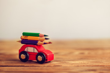 Back to school concept. Miniature Red Car Carrying a colorful pencils on wooden table.