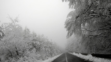 The car is driving on a winter road in a blizzard, POV